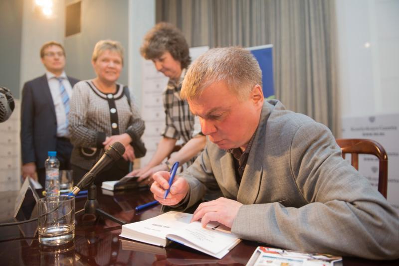 Раздает автографы